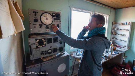 Laurent examine une radio d'antan dans la maison de Denmark Havn. (Photo Evrard Wendenbaum / Naturevolution)