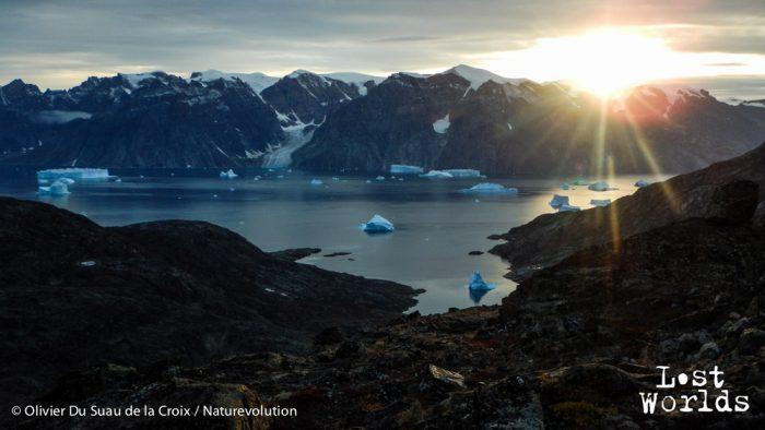 Le soleil se couche derrière les sommets du Renland en jettant ses derniers rayons sur les icebergs de Nordvestfjord.
