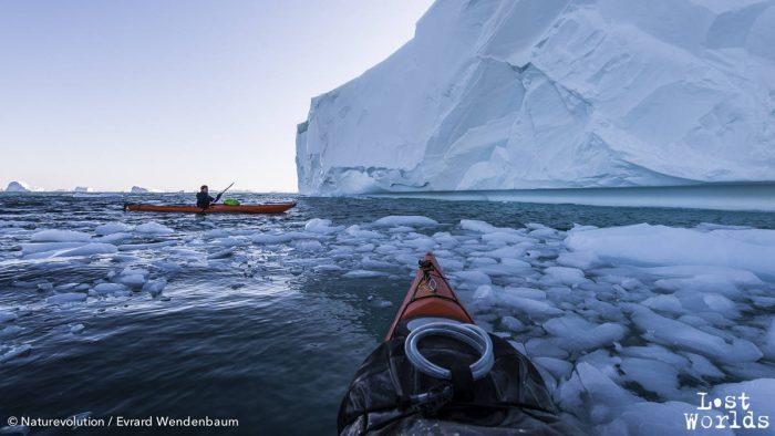Evrard et Aurélie explorent en kayaks les falaises et criques de glace d'un iceberg échoué en face de Sydkap.