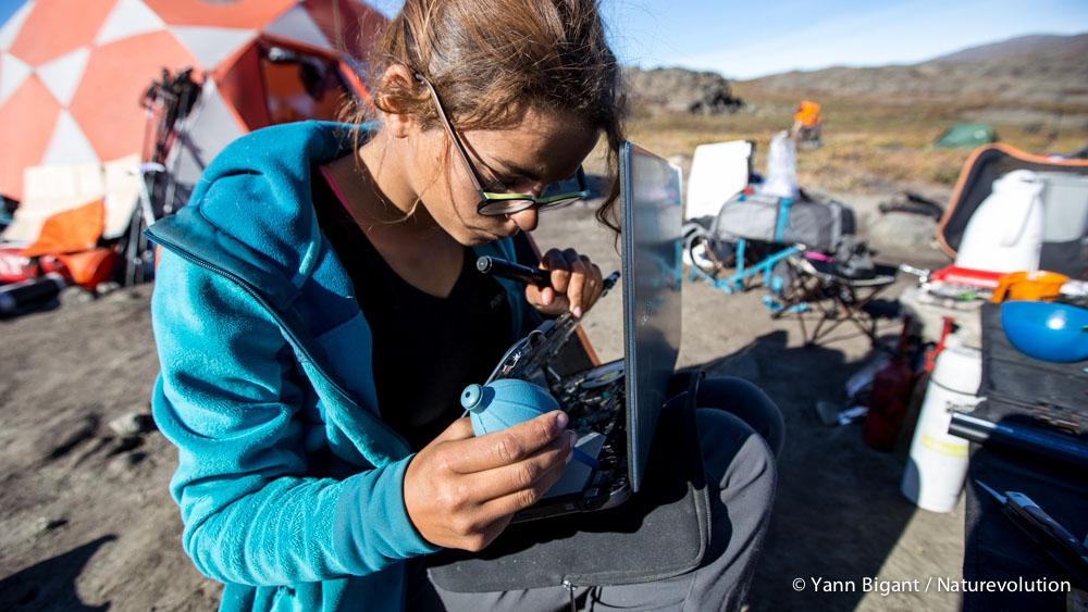 Gaëlle démonte et sèche son ordinateur qui a pris l'eau dans le bateau.